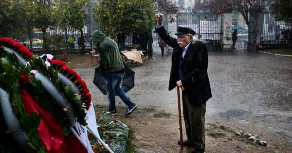 Alone in the rain, resistance fighter Manolis Glezos honors the dead of 1973 Students' Uprising